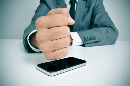 destroying: a businessman sitting in a desk hitting a smartphone with his fist