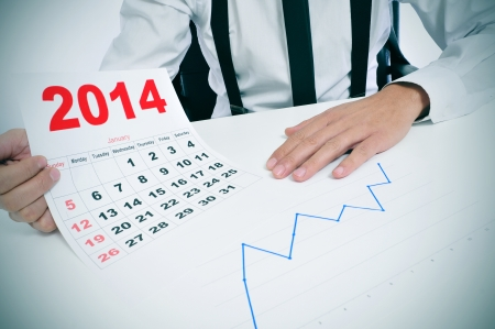 businessman sitting in a desk with a chart and showing a 2014 calendar photo