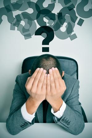 preocupacion: un hombre de negocios sentado en un escritorio con las manos en la cabeza y una nube de signos de interrogación sobre su cabeza