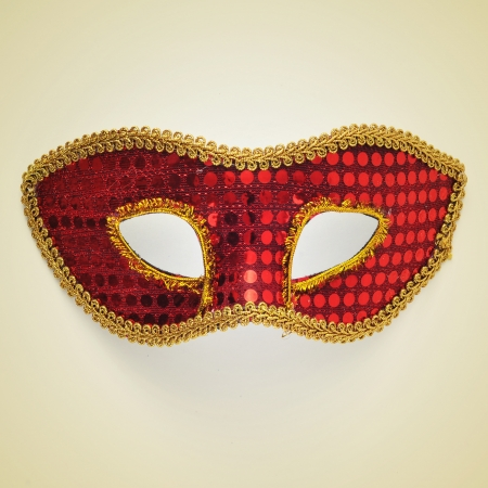 picture of a red and gold carnival mask on a beige photo
