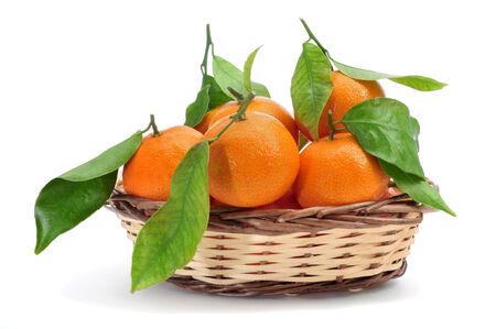 mandarin oranges: some mandarin oranges in a basket on a white Stock Photo