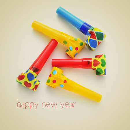blow out: picture of some party horns of different colors and the sentence happy new year on a beige Stock Photo