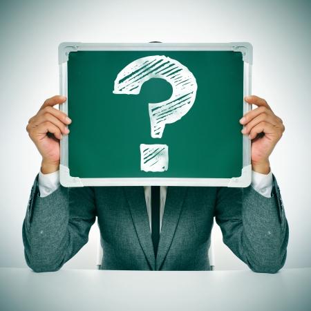preocupacion: hombre que llevaba un traje sentado en una mesa de la celebración de una pizarra en frente de su cara con un signo de interrogación escrita en él