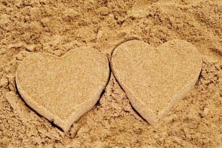 moulded: corazones de arena moldeada en la arena de una playa
