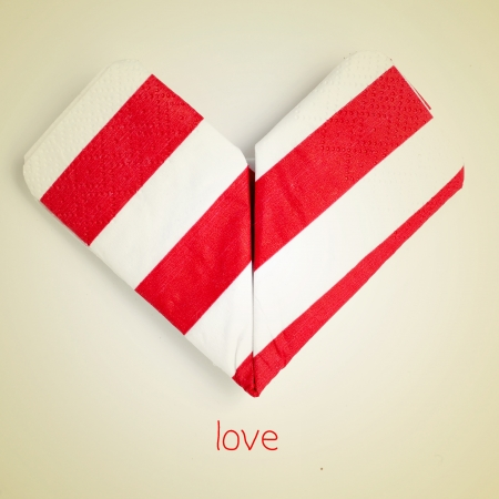 an origami heart and the word love on a beige background with a retro effect photo