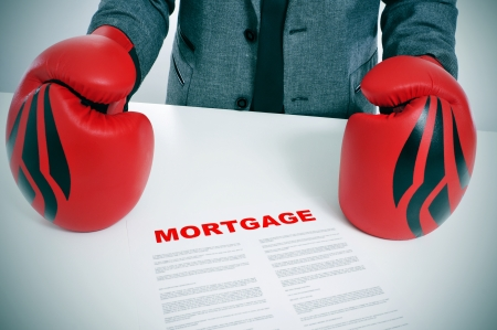 man wearing a suit and boxing gloves with a mortgage contract on his desk photo