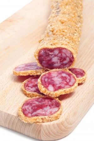embutido: a fuet, a spanish sausage, coated with onion on a chopping board Stock Photo