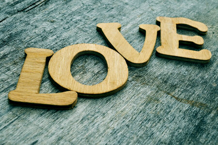wooden letters forming the word love on an old wooden surface photo