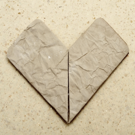 an origami heart made with a wrinkled old paper on a granite background with a retro effect photo