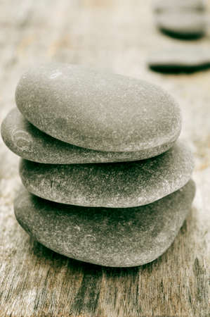 a stack of balanced stones on an old wooden surface photo