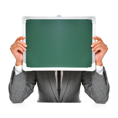 man wearing a suit sitting in a table holding a blank chalkboard in front of his face  photo