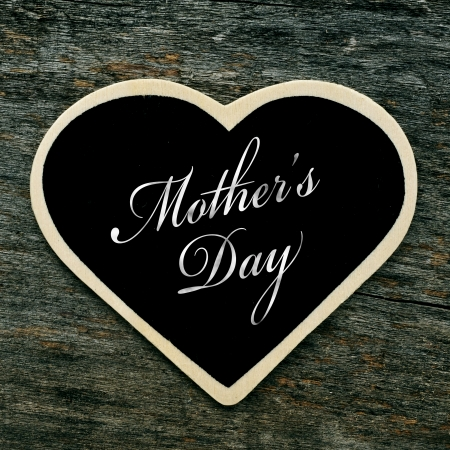 a heart-shaped blackboard with the text mothers day written in it on an old wooden surface photo