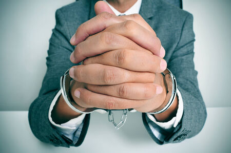 forger: a man wearing a suit sitting in a desk, with handcuffs in his wrists
