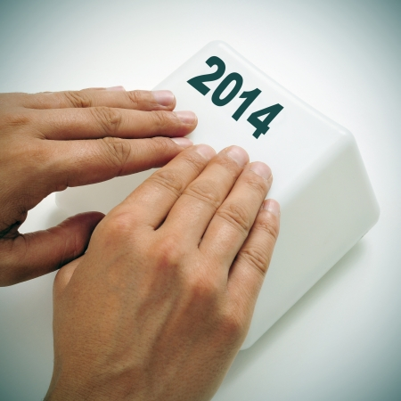 a man pressing a giant key with the number 2014, as the new year, with his hands Stock Photo - 24817828