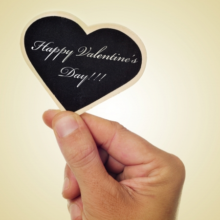 picture of a man hand holding a heart-shaped chalkboard with the sentence happy valentines day written in it, with a retro effect photo