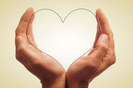 man hands holding a silhouette of a heart, with a retro effect photo