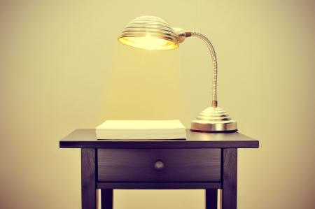 suspenso: la imagen de una lámpara de cuello de cisne de edad y una pila de hojas de papel en blanco en una oficina, con un efecto retro Foto de archivo