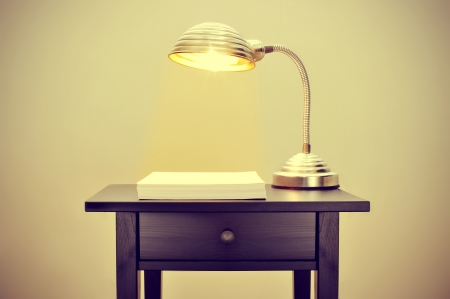 picture of an old gooseneck lamp and a stack of blank paper sheets on a bureau, with a retro effect photo