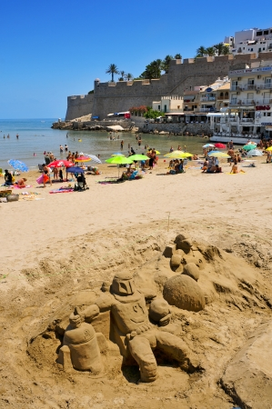 bathers: Peniscola, Spain - July 26, 2013  Sand sculpture and bathers in North Beach, facing the castle in Peniscola, Spain, a typical summer destination in the North of the Valencian Community