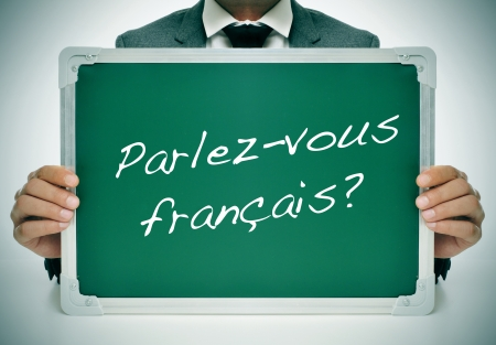 french text: man wearing a suit holding a chalkboard with the question parlez-vous francais? do you speak french? written in it