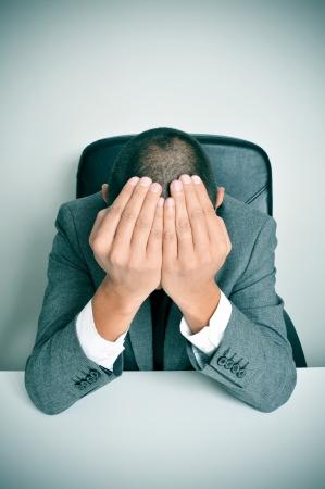 ein Geschäftsmann sitzt in einem Schreibtisch mit den Händen in den Kopf Standard-Bild