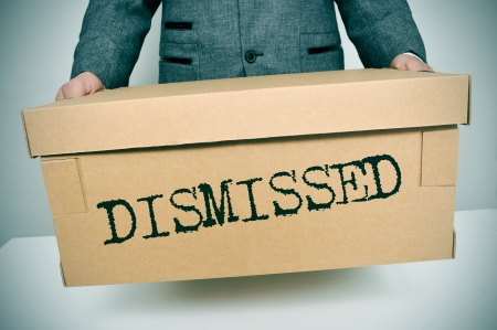 ruination: a businessman carrying a box with the word dismissed written in it