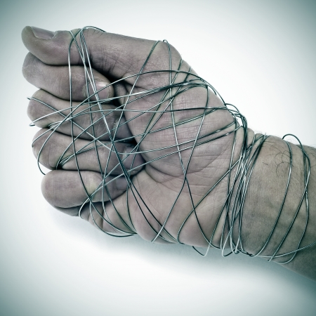 oppression: man hand tied with wire, as a symbol of oppression or repression