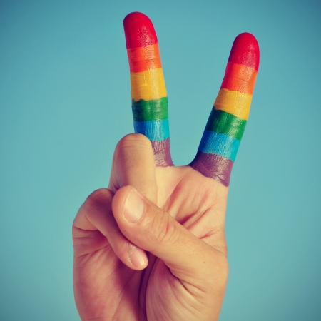 a hand making the V sign with fingers painted as the rainbow flag photo