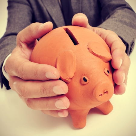 pennypinching: a man wearing a suit sitting in a desk with a piggy bank in his hands Stock Photo