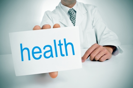 a man wearing a white coat showing a signboard with the word health written in it Stock Photo - 25095473