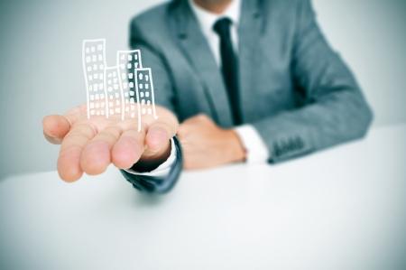 biznesmen siedzi na biurko pokazując stos opracowanych budynków w ręku
