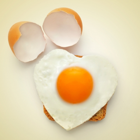 a heart-shaped fried egg on a toast and the cracked shell on a beige background, with a retro effect photo
