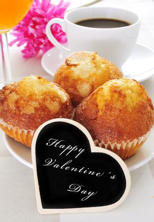 Un desayuno continental que incluye magdalenas, café y jugo y la condena día de san valentín feliz escrito en una pizarra con forma de corazón Foto de archivo - 25100754