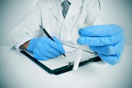 그의 손에 정액 샘플을 들고 코트와 파란색 의료 장갑을 착용하는 남자