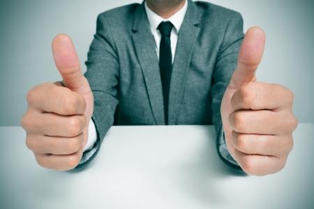信号を親指を与えるテーブルに座っているスーツを着た男 写真素材