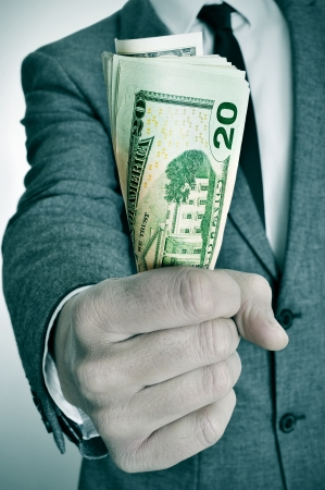 bribe: a man wearing a suit sitting with a wad of american dollar bills in his hand