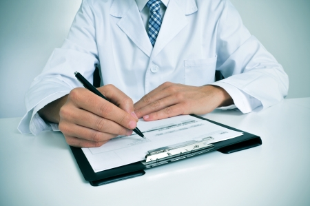 a doctor sitting in the desk of his consulting room writing in a clipboard photo