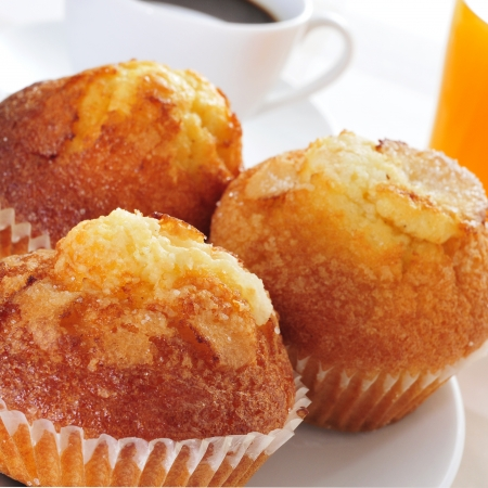 madalena: a plate with some magdalenas, typical spanish plain muffins, and a cup of coffee and a glass of orange juice