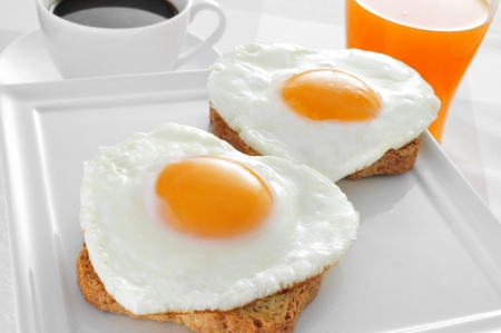 somme heart-shaped fried eggs served on bread, a cup of coffee and a glass of orange juice on a set table Stock Photo
