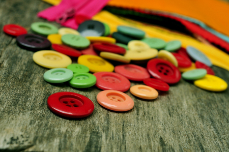 notions: a pile of buttons, fabric and zippers of different colors on an old wooden table