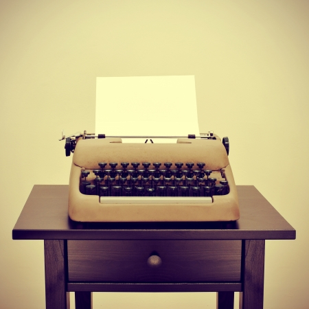 detective agency: an old typewriter with a blank page on a desk, with a retro effect