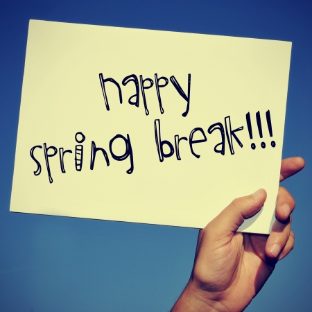 eastertime: a man hand holding a signboard with the text happy spring break written in it Stock Photo