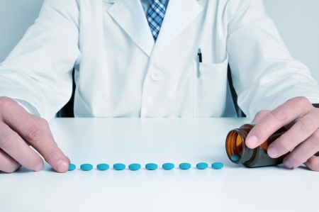 generic: a doctor sitting in a desk with a pile of blue pills Stock Photo