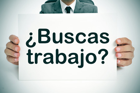 a man wearing a suit holding a signboard with the question buscas trabajo? are you looking for a job? written in spanish photo