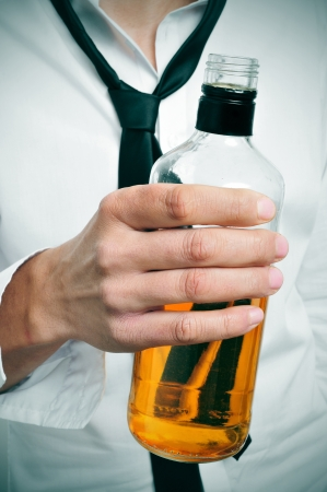 intoxication: a drunk businessman with a bottle of whiskey in his hand
