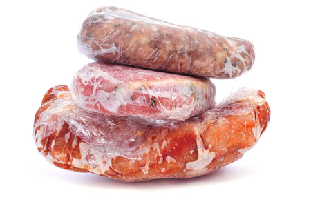 Frozen meat: frozen sausages and different meat wrapped in plastic on a white background