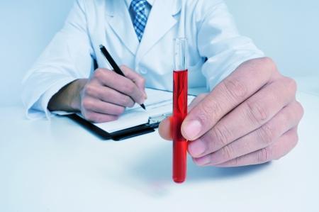 그의 손에 혈액 샘플을 들고 코트와 파란색을 착용하는 남자