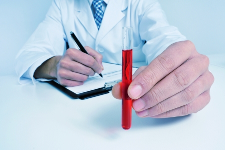 a man wearing white coat and blue holding a blood sample in his hand Stock Photo