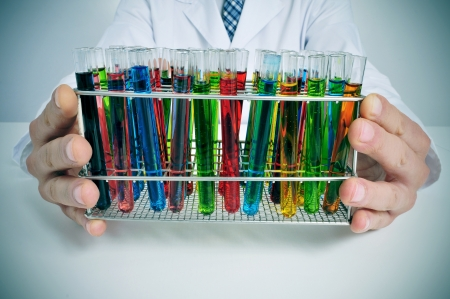 assays: man in white coat with test tubes with liquids of different colors in a laboratory Stock Photo