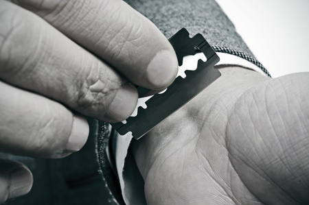 cut wrist: businessman trying to cut his wrist with a razor blade